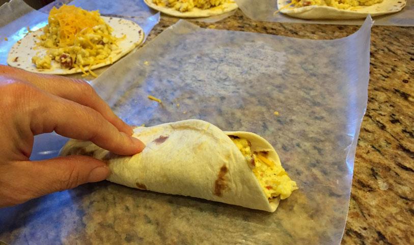 rolling up breakfast burrito on wax paper, breakfast recipe