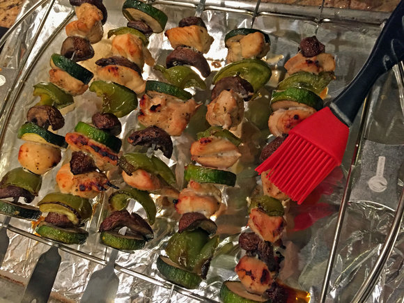 chicken kebabs on kabob skewers and stand with basting brush