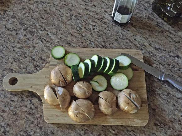 mushrooms, zucchini on cutting board with knife, kebab prep
