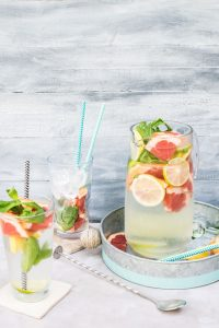 fruit infused water in pitcher and glasses on tray